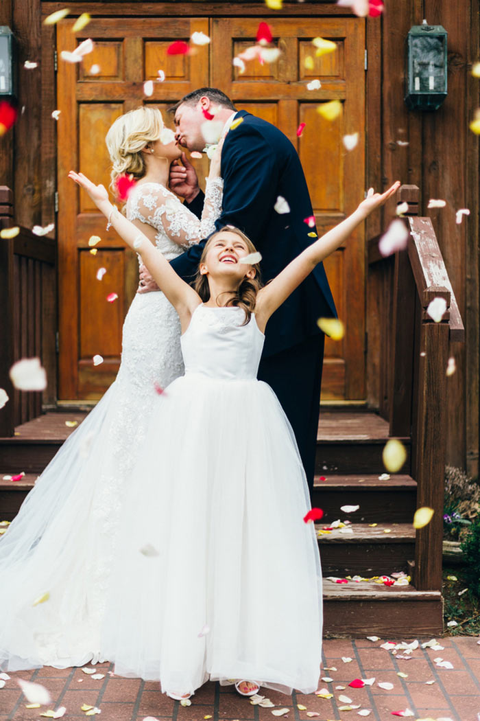 flower girl throwing rose petals as bride and groom kiss