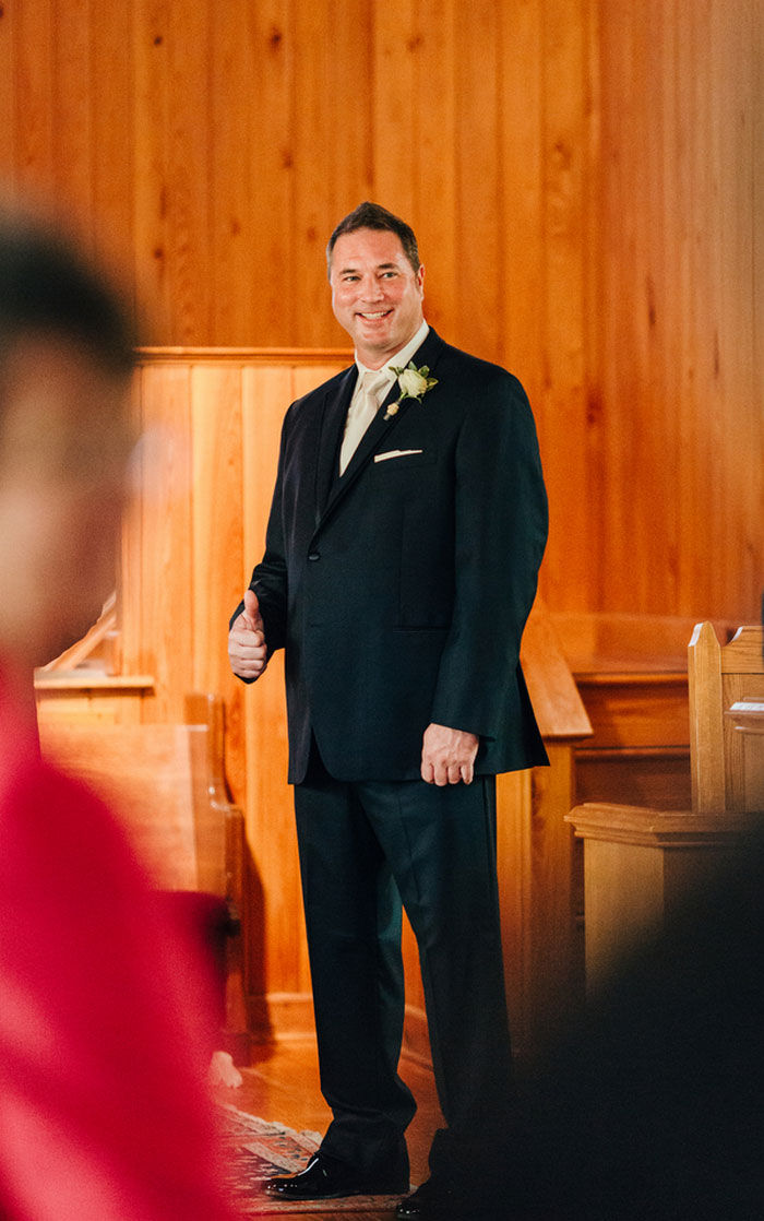 groom standing at the altar giving thumbs up