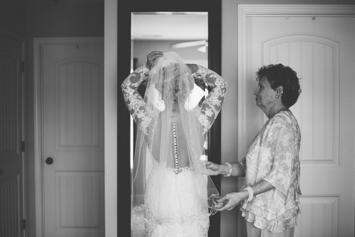 bride adjusting her veil in the mirror