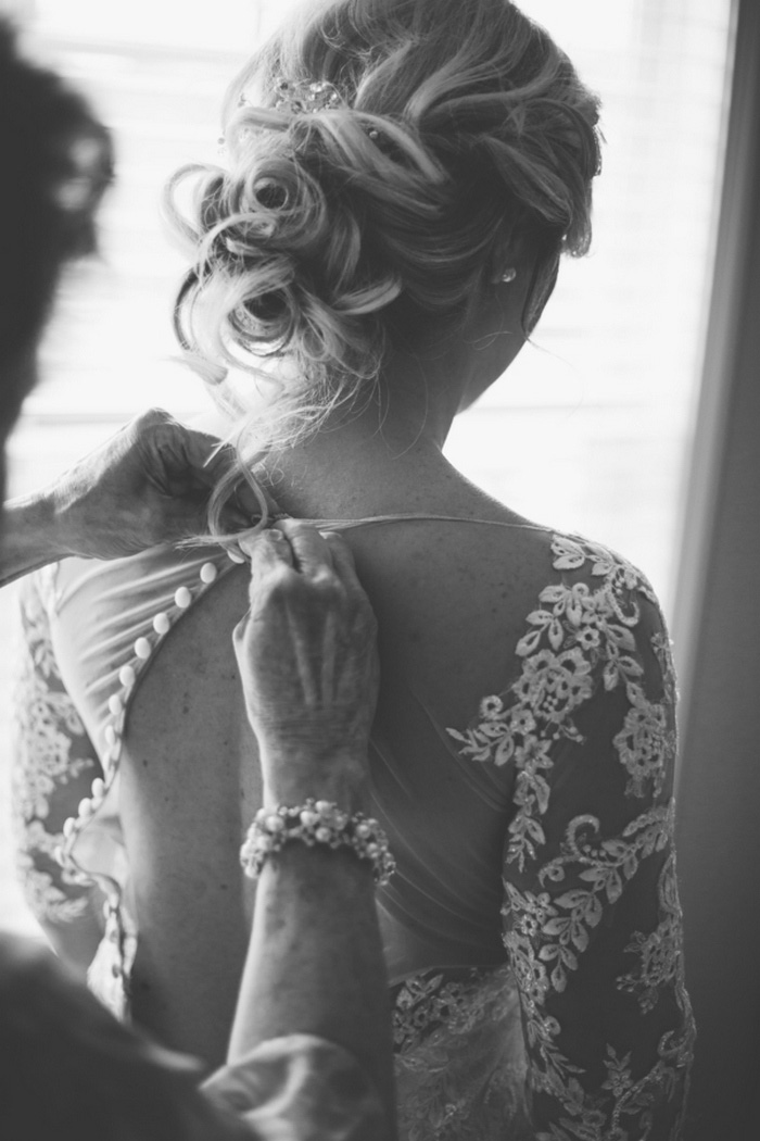 bride having her dress buttoned up the back