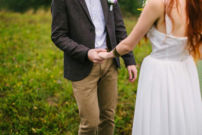 groom holding bride's hand during ceremony