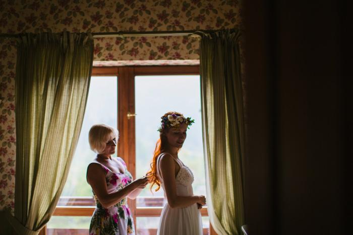 bride getting zipped into her wedding dress