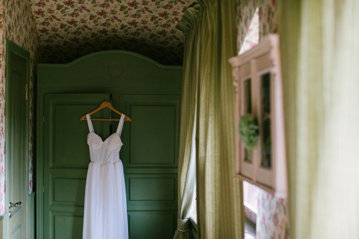 wedding dress hanging up on armoire