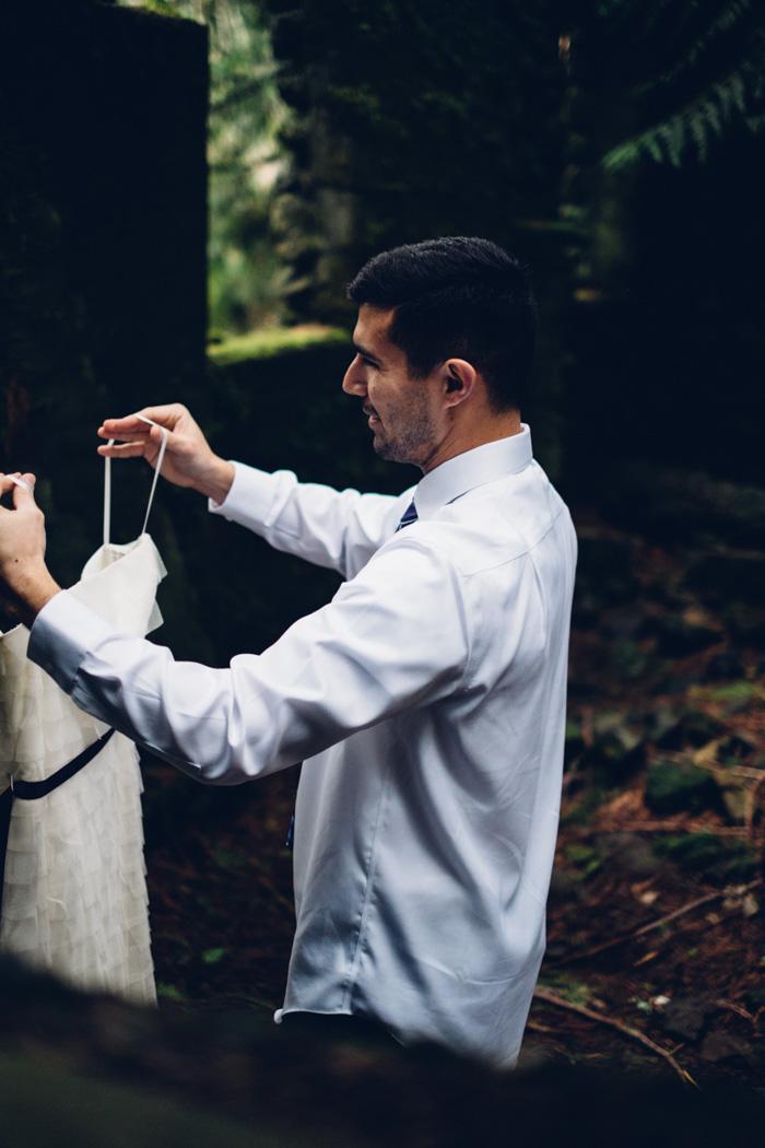 groom carrying wedding dress