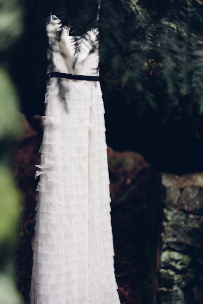 wedding dress hanging up on the woods