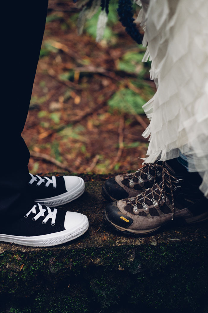 photo of groom's sneakers and bride's hiking boots