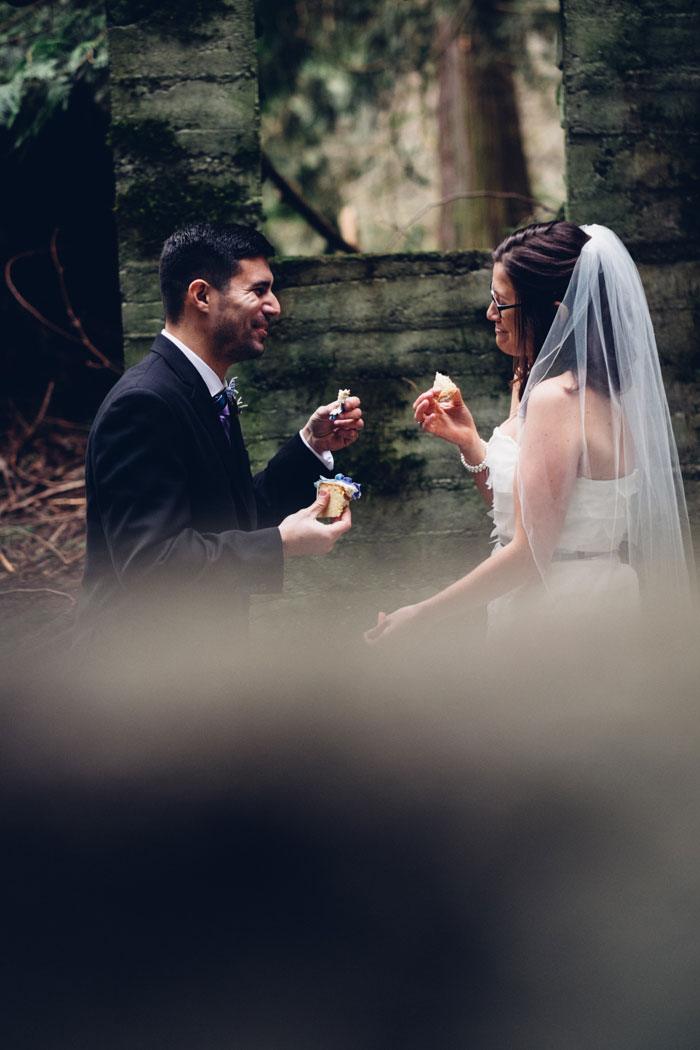 bride and groom eating cake in the woods