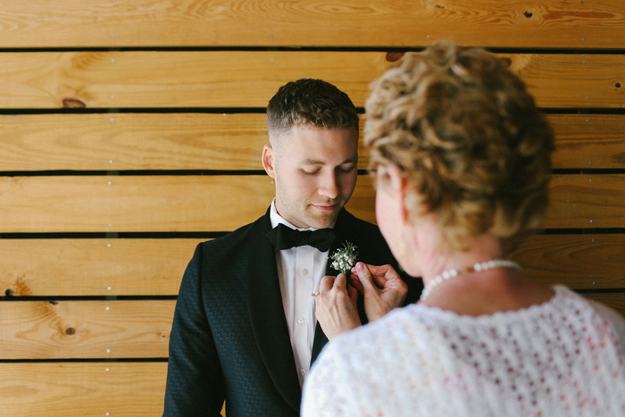 groom having boutonnière pinned on