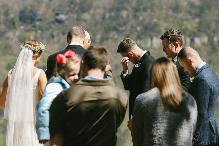 groom wiping away tears as bride walks down the aisle