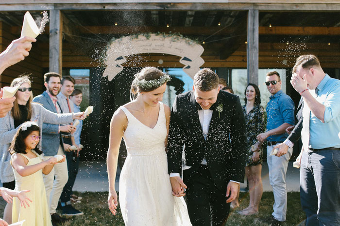 guests throwing lavender confetti on bride and groom
