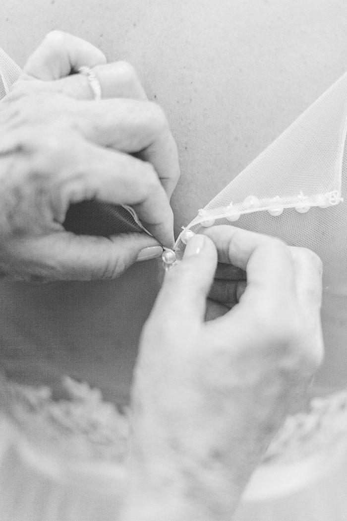 hands buttoning wedding dress