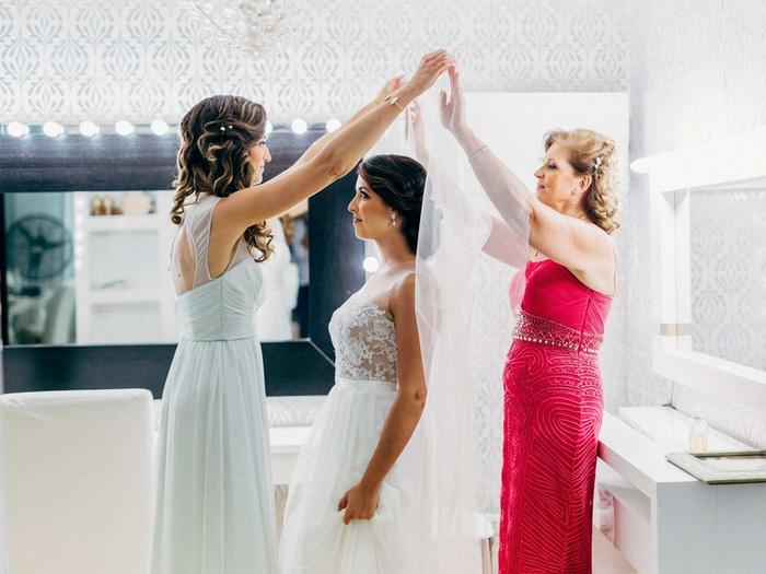 bridesmaids putting bride's veil on