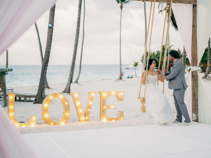 bride and groom portrait on the beach with love sign