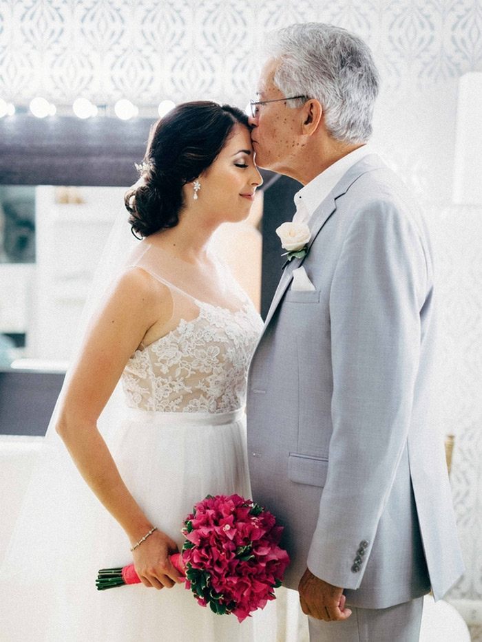 father of the bride kissing bride's forehead