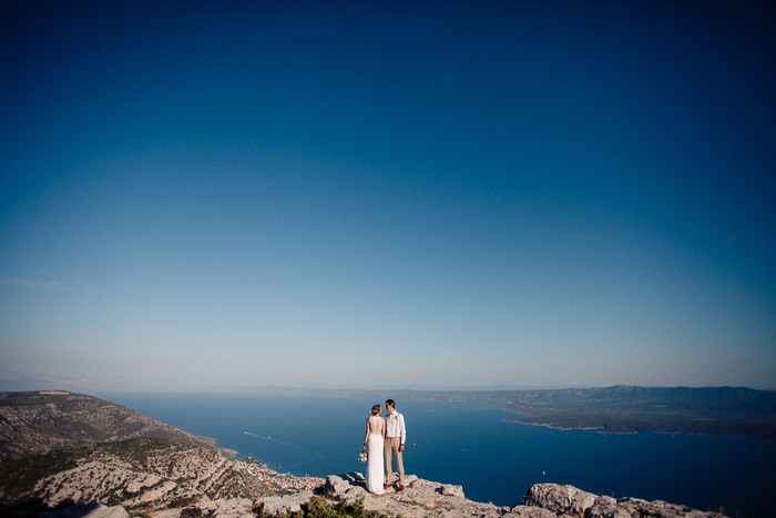 bride and groom looking over the ocean