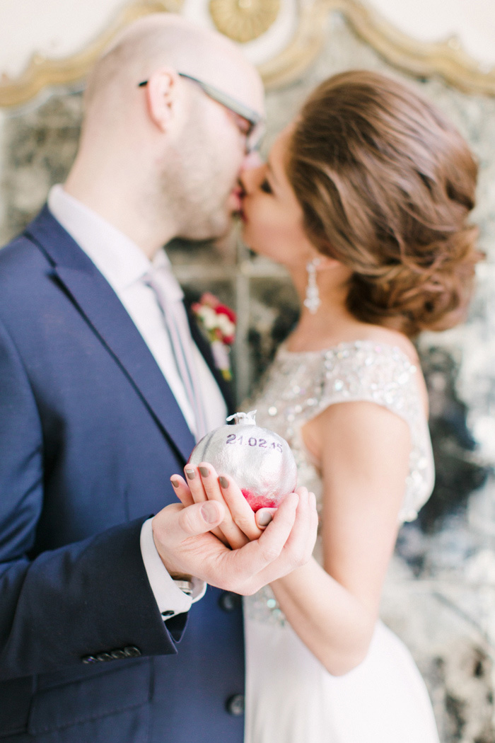 bride and groom holding pomegranate with wedding date
