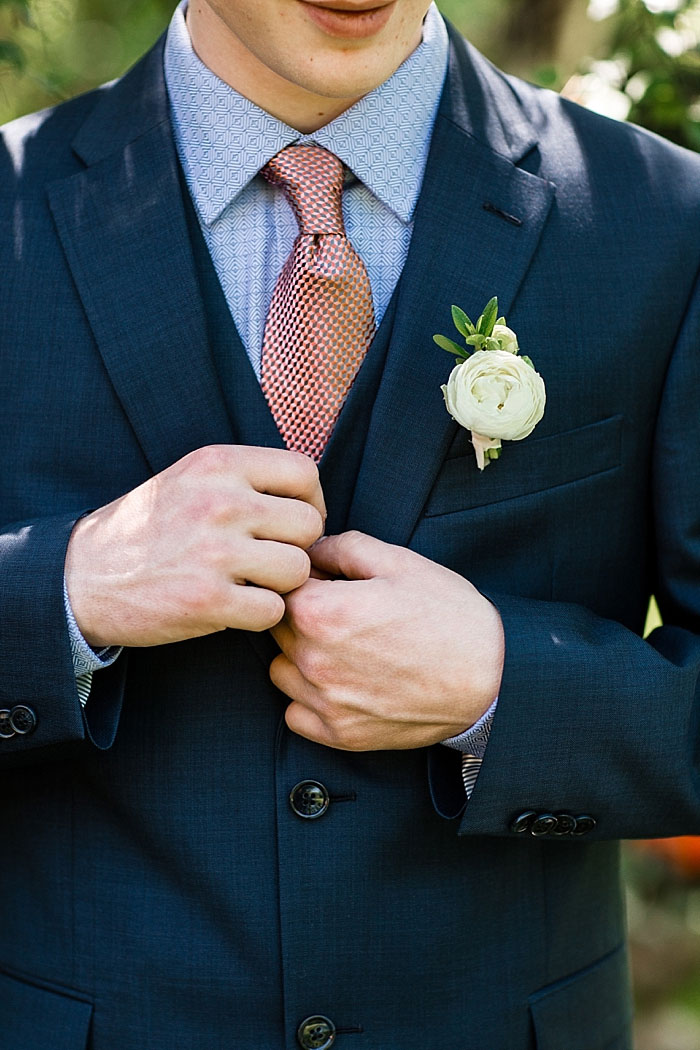 groom buttoning jacket