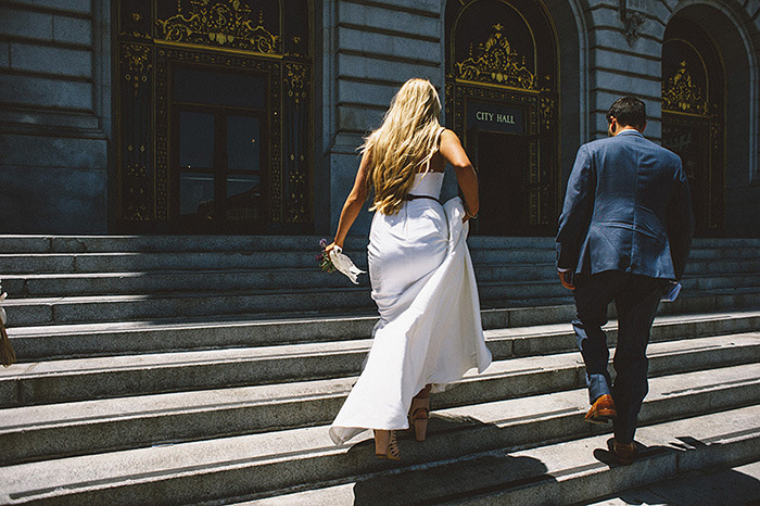 bride and groom walking up steps of San Francisco City Hall