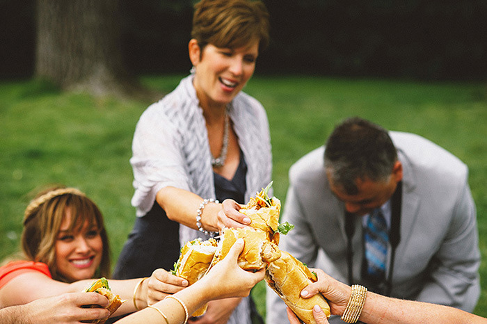 wedding guests toasting with sandwiches in the park