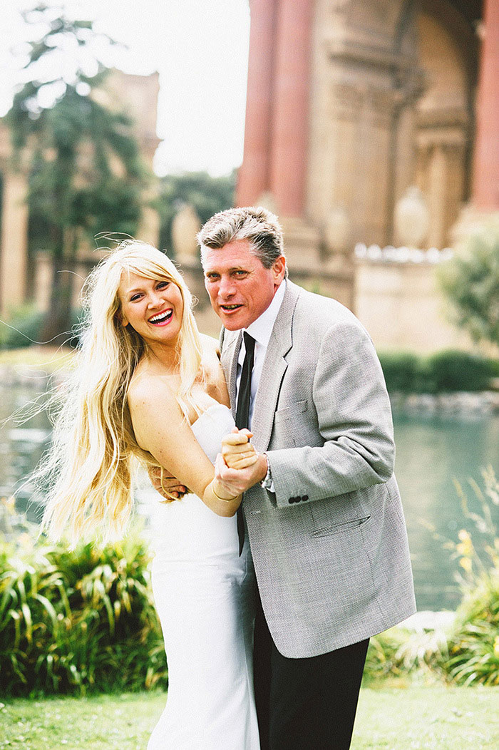 bride and father dancing in the park