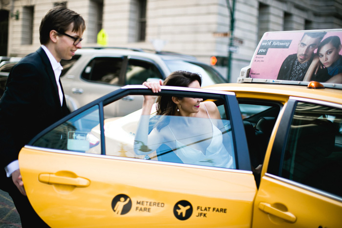bride getting into yellow taxi