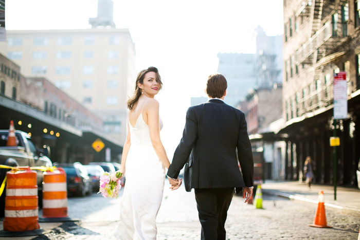 bride looking over shoulder while walking with groom