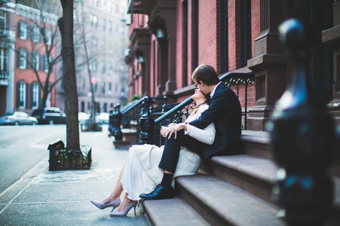 bride and groom kissing on stoop