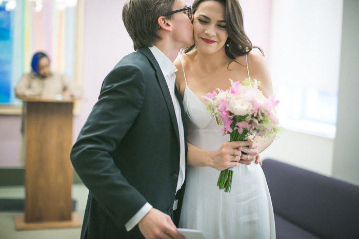 groom kissing bride at city hall elopement