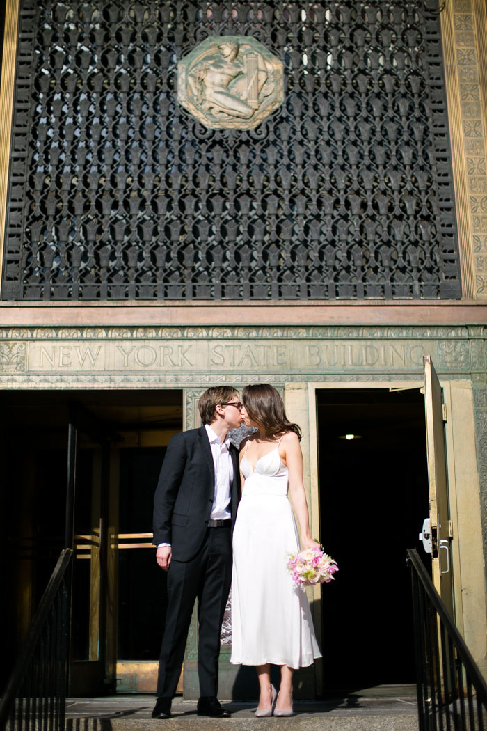 bride and groom kissing in front of city Hall