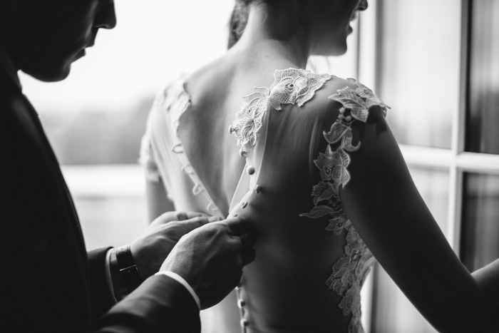 groom buttoning bride's dress