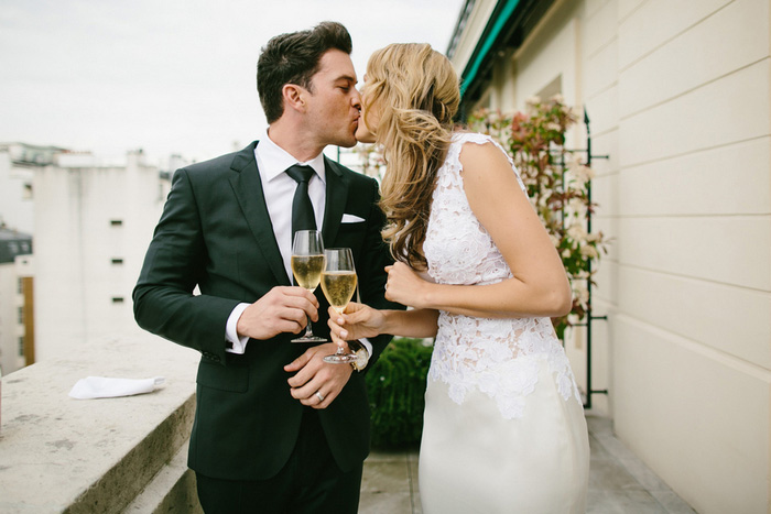 bride and groom kissing with champagne glasses