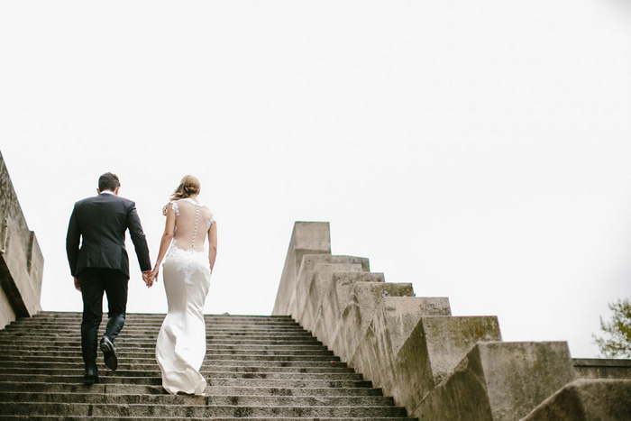 bride and groom climbing stairs in Paris