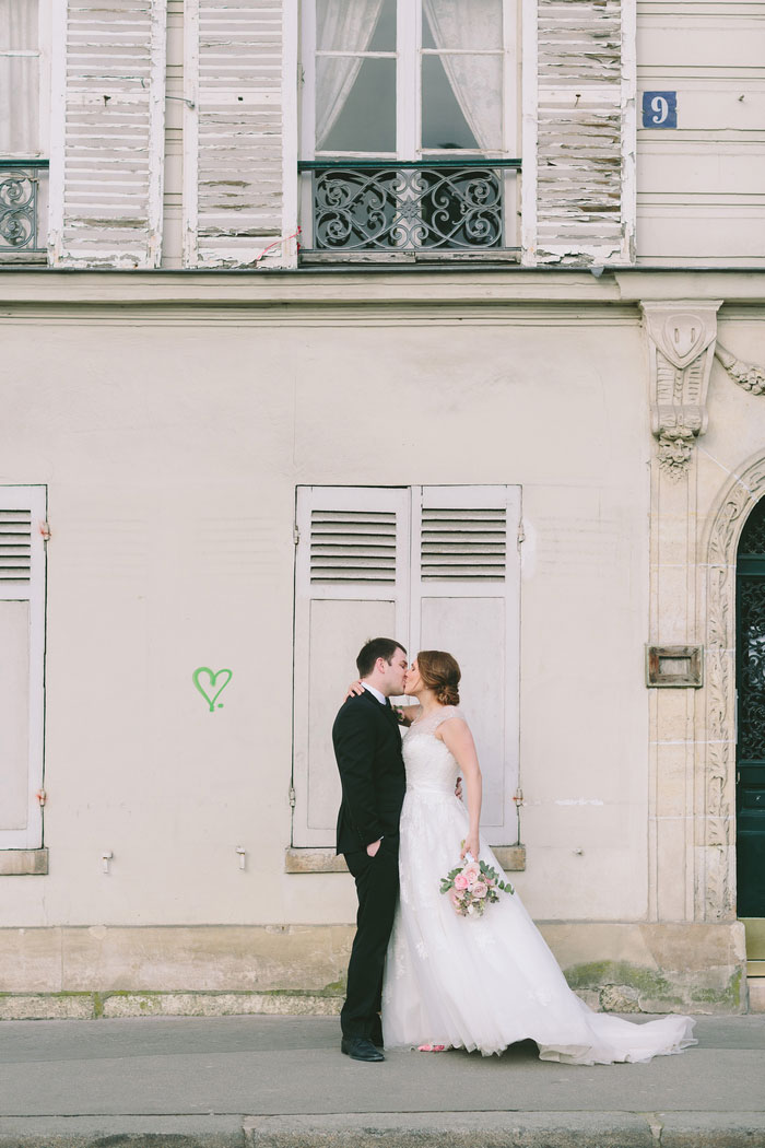 bride and groom kissing in front of heart graffiti