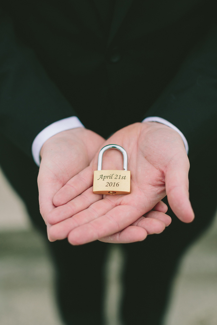 groom holding wedding lock