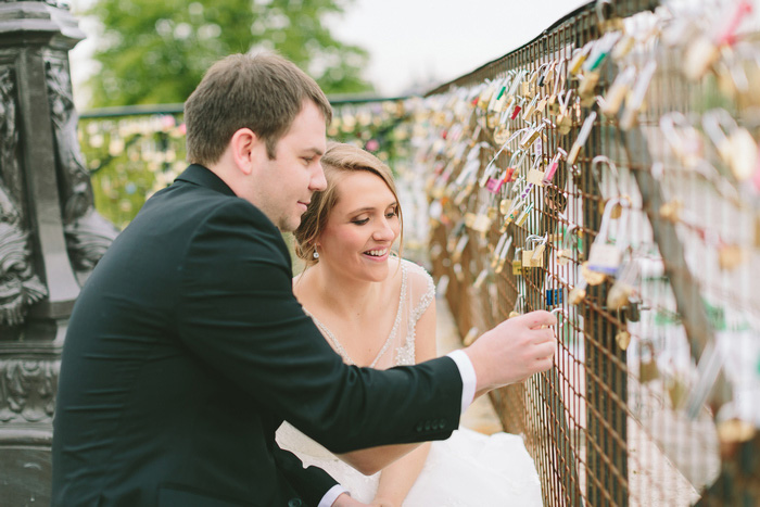 bride and groom putting lock on bridge