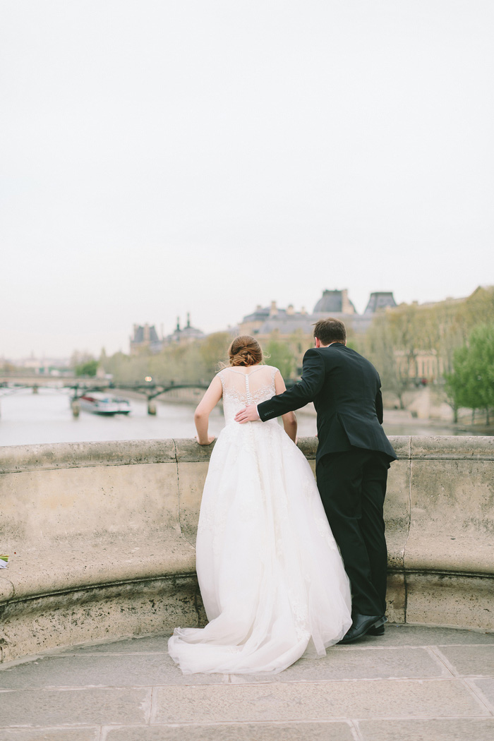 bride and groom looking over bridge into the seine