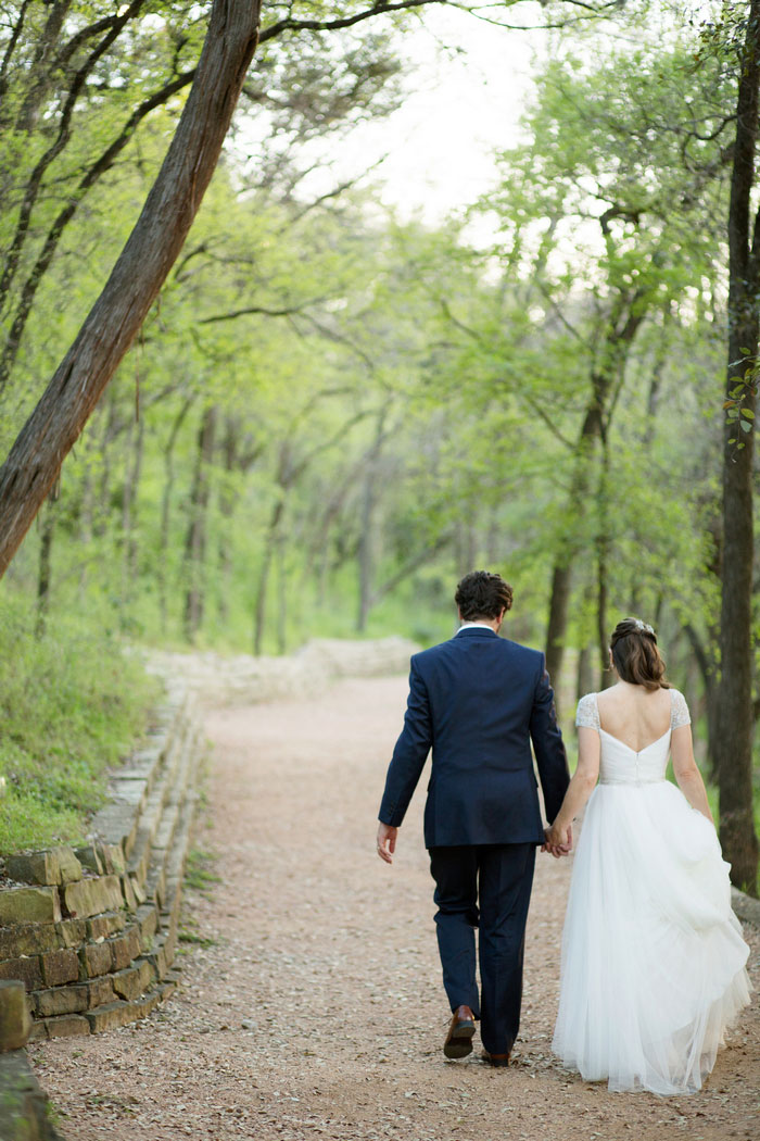 bride and groom walking down wooded path