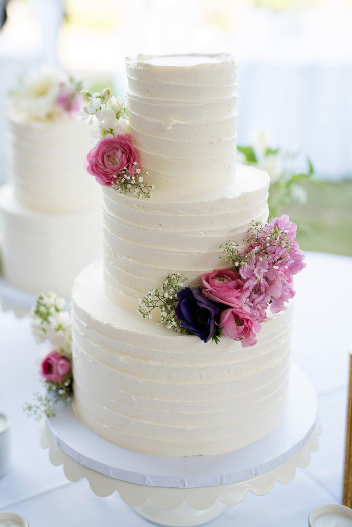 3 tiered white wedding cake with fresh pink flowers