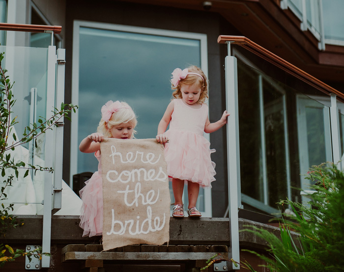 flower girls holding here comes the bride sign