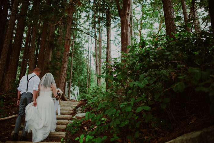 bride and groom climbing steps in the woods