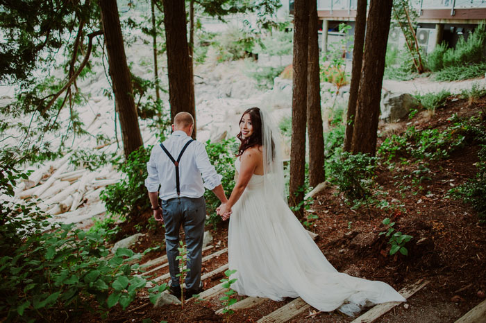 bride looking behind walking down steps in the woods