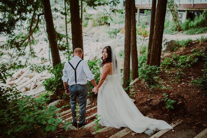 bride looking behind walking down steps in the woods
