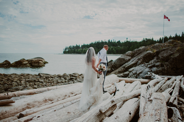 bride and groom walking on rocky beach