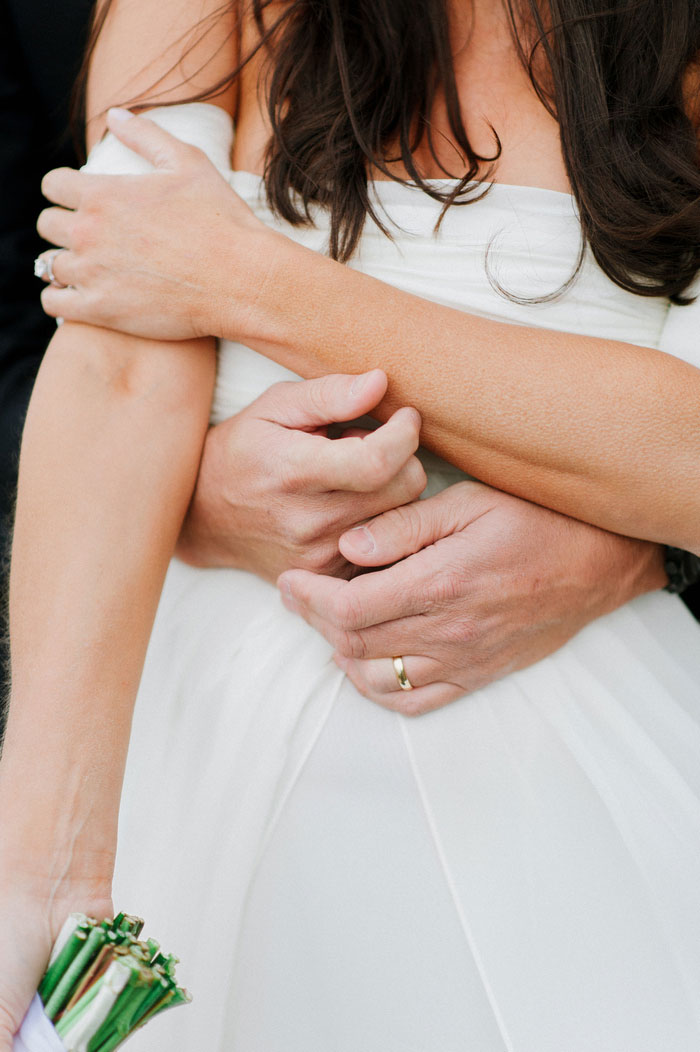 bride with groom's arms wrapped around her