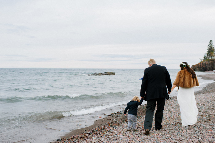 bride, groom, and son walking on the beach
