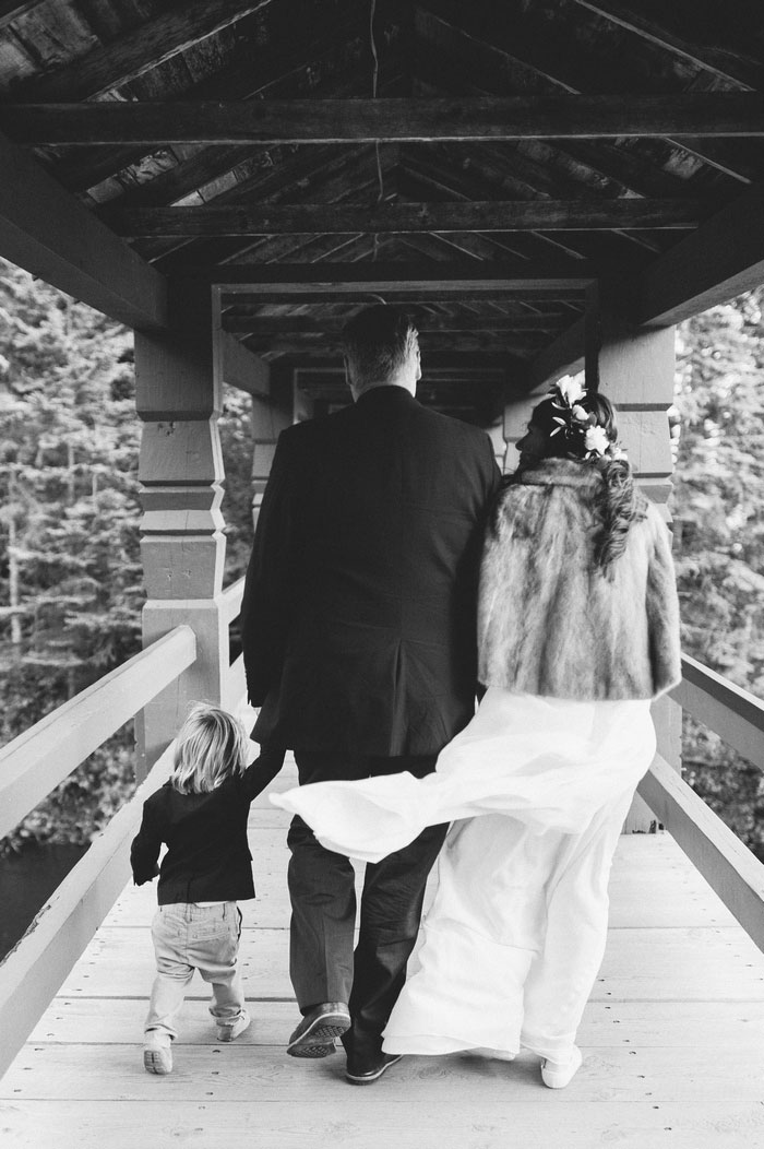 bride, groom, and son walking on covered bridge