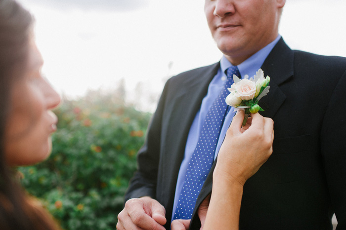 groom geting boutonniere pinned on