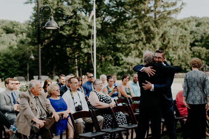 groom hugging guest at ceremony