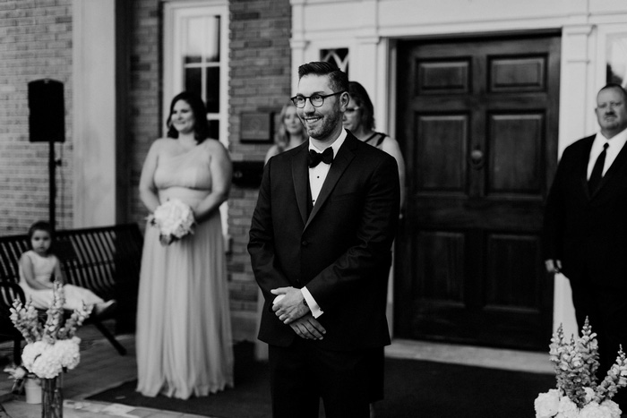 groom watching bride walk up the aisle