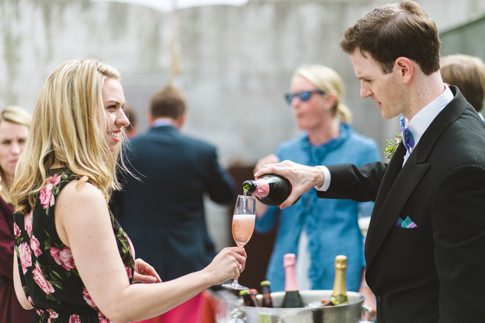 groom pouring bride champagne